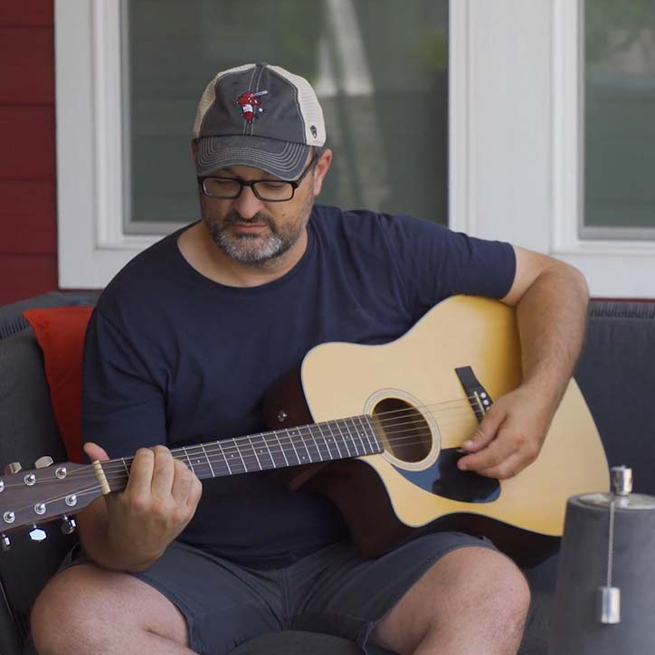 Jeff Mores playing guitar on back porch